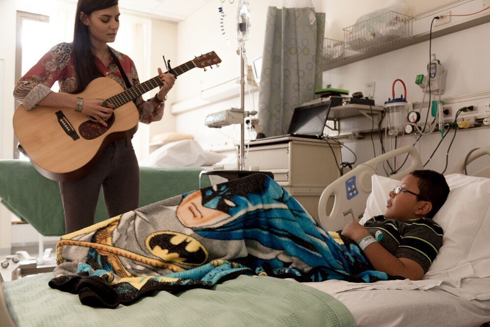 Nilu sings at the bedside of a young patient.